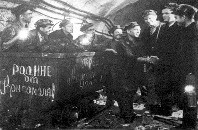 """შახტმშენებლი სამმართველოს უფროსი ნოდარ მეძმარიაშვილი ულოცავს მეშახტეთა ბრიგადას პირველი ქვანახშირის მოპოვებას. ფოტო გაზეთ """"პრავდიდან"""" 25 აგვისტო, 1957 წ."""